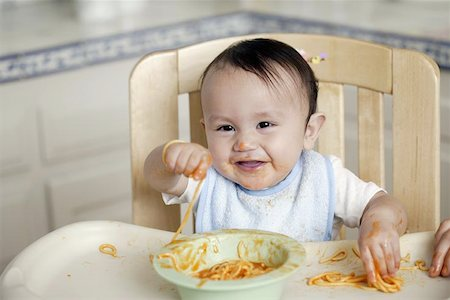 Baby eating in high chair Stock Photo - Premium Royalty-Free, Code: 621-01005062