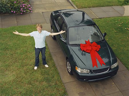 Teen Boy with Arms Outstretched Next to His New Car Stock Photo - Premium Royalty-Free, Code: 621-01008462