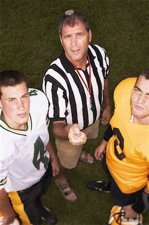 Referee tossing coin in front of football players Stock Photo - Premium Royalty-Free, Code: 621-01201393