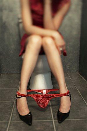 Woman sitting on toilet Stock Photo - Premium Royalty-Free, Code: 621-01225330