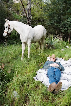 Cowboy sleeping near horse Stock Photo - Premium Royalty-Free, Code: 621-01225468