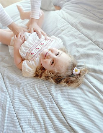 Little Girl Lying On Bed Stock Photo - Premium Royalty-Free, Code: 621-01230237