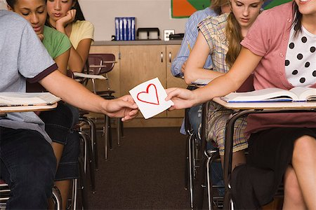 passing of papers in the classroom - Teenage boy and teenage girl passing notes in classroom Stock Photo - Premium Royalty-Free, Code: 621-01265220