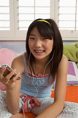 preteen  smile  one  alone - Preteen girl holding MP3 player Stock Photo - Premium Royalty-Free, Code: 621-01305696