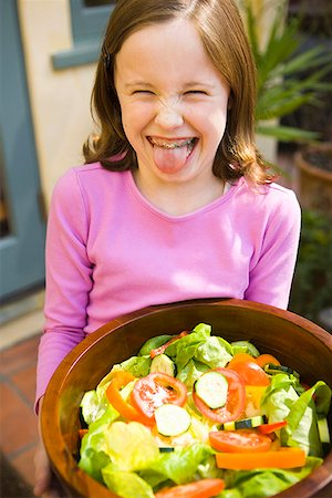 Girl sticking out tongue while holding bowl of salad Stock Photo - Premium Royalty-Free, Code: 621-01519904