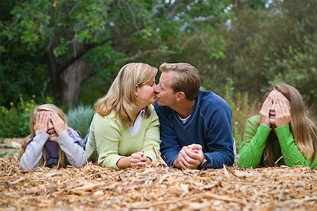 Couple kissing while kids cover eyes Stock Photo - Premium Royalty-Free, Code: 621-01554092