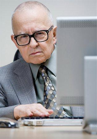 Grumpy senior man sitting at desk Stock Photo - Premium Royalty-Free, Code: 621-01775750