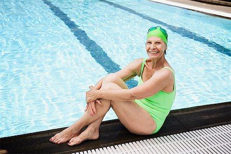 seniors and swim cap - Smiling senior woman swimmer seated at pool edge Stock Photo - Premium Royalty-Free, Code: 621-01800078