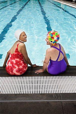 seniors and swim cap - Smiling senior woman swimmers seated at pool edge Stock Photo - Premium Royalty-Free, Code: 621-01800087