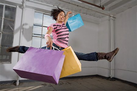 Woman in midair with shopping bags Stock Photo - Premium Royalty-Free, Code: 621-01800399