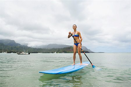 Woman on surfboard with paddle Stock Photo - Premium Royalty-Free, Code: 621-02027905