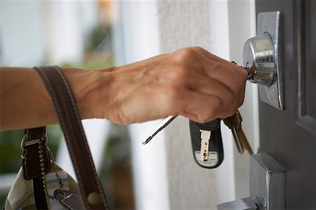Hand with keys unlocking door Stock Photo - Premium Royalty-Free, Code: 621-02028184