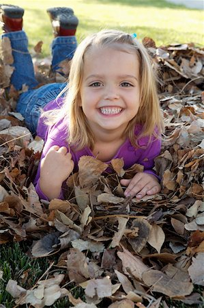 pile leaves playing - Smiling girl in pile of leafs Stock Photo - Premium Royalty-Free, Code: 621-02085256