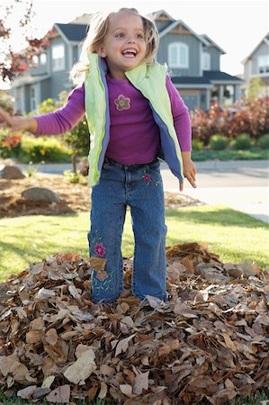 pile leaves playing - Smiling girl jumping in pile of leafs Stock Photo - Premium Royalty-Free, Code: 621-02085257