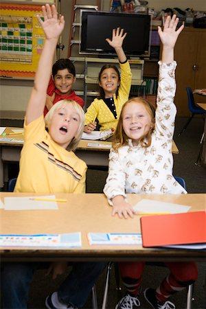Children at desks raising hands Stock Photo - Premium Royalty-Free, Code: 621-02085729