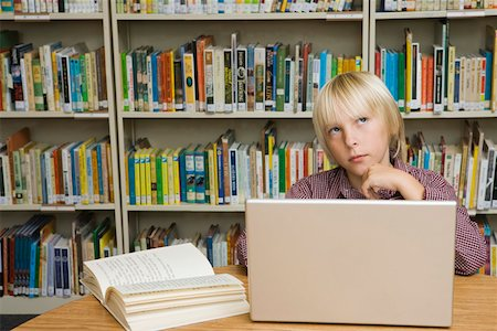 Boy thinking in library with laptop computer and book Stock Photo - Premium Royalty-Free, Code: 621-02085811