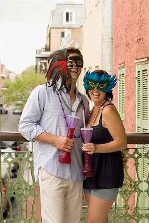 Couple with masquerade masks on balcony with drinks Stock Photo - Premium Royalty-Free, Code: 621-02279712