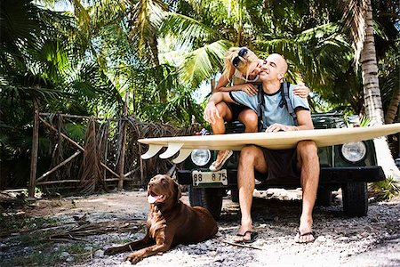 dog kissing man - Couple sitting on car with surfboard and dog Stock Photo - Premium Royalty-Free, Code: 621-02357790