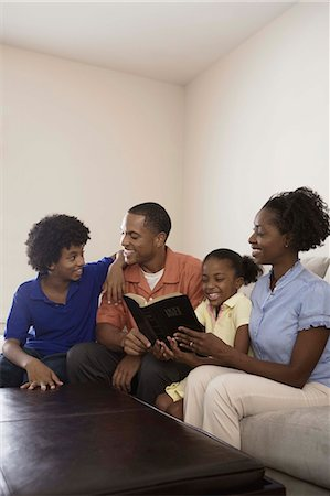 Family sitting on couch and reading Holy Bible Stock Photo - Premium Royalty-Free, Code: 621-03569495