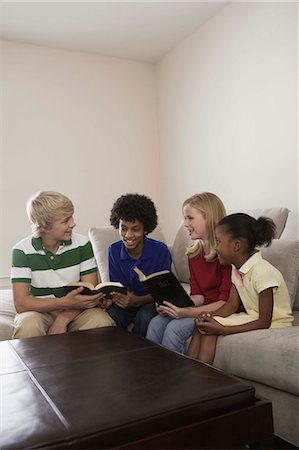 Children sitting on couch and reading Holy Bible Stock Photo - Premium Royalty-Free, Code: 621-03569497