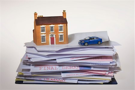 model house and toy car on stack of overdue bills Stock Photo - Premium Royalty-Free, Code: 621-03768744