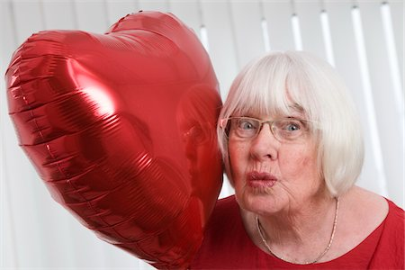senior woman with heart balloon, blowing a kiss Stock Photo - Premium Royalty-Free, Code: 621-03778734