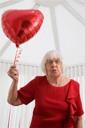 senior woman with heart balloon, blowing a kiss Stock Photo - Premium Royalty-Free, Code: 621-03778737