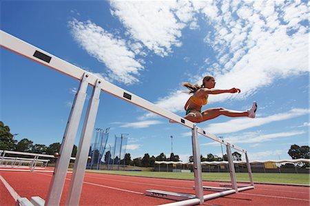 Female Athlete Clearing Hurdles Stock Photo - Premium Royalty-Free, Code: 622-05602839