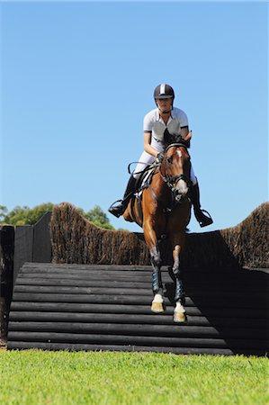 equestrian - Young Woman Horseback Rider Jumping Hurdle Stock Photo - Premium Royalty-Free, Code: 622-05786779