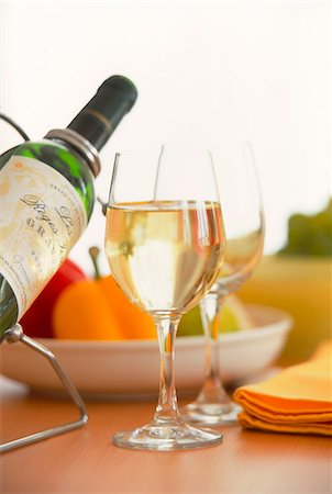 Drinking Glass, Wine Bottle And Fruit Bowl On Table Stock Photo - Premium Royalty-Free, Code: 622-06009627