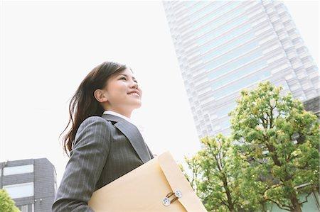 Businesswoman with envelope walking Stock Photo - Premium Royalty-Free, Code: 622-06900446