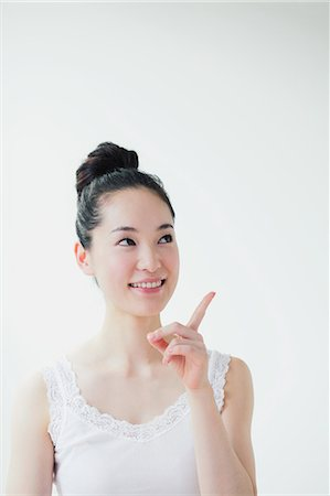 Young woman pointing finger up smiling Stock Photo - Premium Royalty-Free, Code: 622-06964288