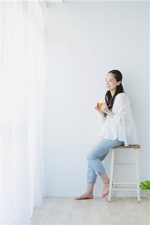 Young woman sitting with cup of tea in the living room Stock Photo - Premium Royalty-Free, Code: 622-06964306