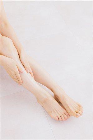 foot massage - Woman massaging her legs on the floor Stock Photo - Premium Royalty-Free, Code: 622-06964375