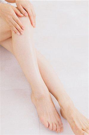 foot massage - Woman massaging her legs on the floor Stock Photo - Premium Royalty-Free, Code: 622-06964376