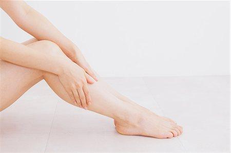 foot massage - Woman massaging her legs on the floor Stock Photo - Premium Royalty-Free, Code: 622-06964378