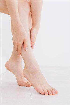 foot massage - Woman massaging her legs on the floor Stock Photo - Premium Royalty-Free, Code: 622-06964379