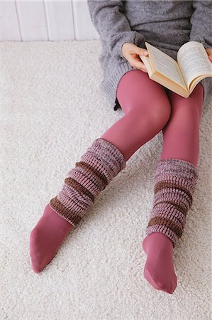 Woman with leg warmers reading a book on the floor Stock Photo - Premium Royalty-Free, Code: 622-06964370
