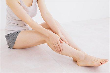 foot massage - Woman massaging her legs on the floor Stock Photo - Premium Royalty-Free, Code: 622-06964380