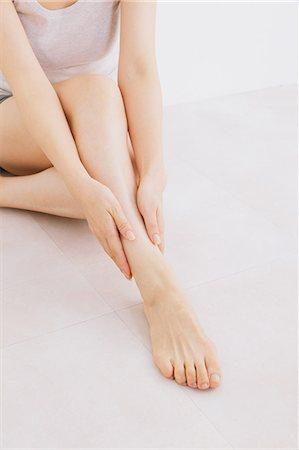foot massage - Woman massaging her legs on the floor Stock Photo - Premium Royalty-Free, Code: 622-06964381
