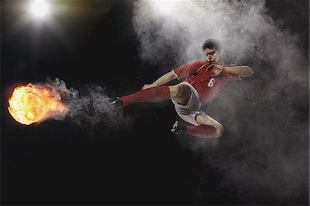 footballeur - Soccer Player Kicking The Ball In Mid-Air Stock Photo - Premium Royalty-Free, Code: 622-07736025