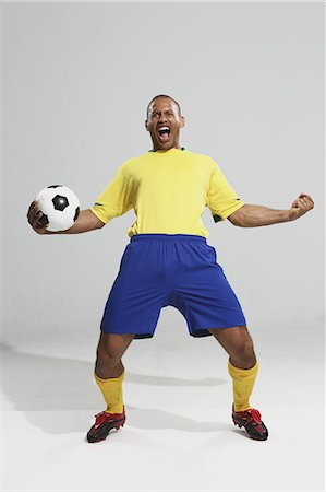 soccer fan - Football player in a yellow and blue uniform standing against white background Stock Photo - Premium Royalty-Free, Code: 622-07736034