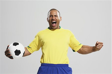 soccer fan - Football player in a yellow and blue uniform standing against white background Stock Photo - Premium Royalty-Free, Code: 622-07736035