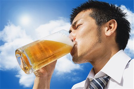sweaty businessman - Japanese businessman drinking draft beer Stock Photo - Premium Royalty-Free, Code: 622-07810652
