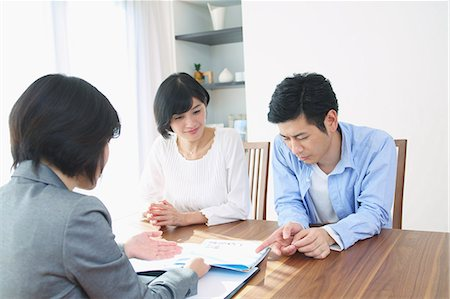descriptive - Young Japanese couple consulting with financial planner Stock Photo - Premium Royalty-Free, Code: 622-08122699