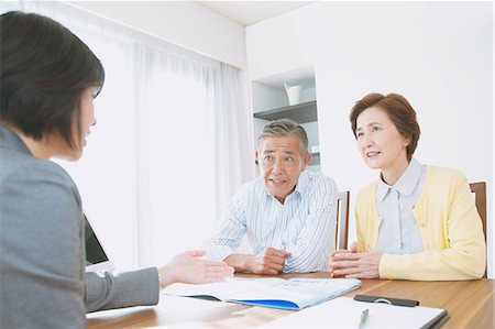 descriptive - Senior Japanese couple consulting with financial planner Stock Photo - Premium Royalty-Free, Code: 622-08122705