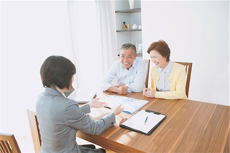 descriptive - Senior Japanese couple consulting with financial planner Stock Photo - Premium Royalty-Free, Code: 622-08122706