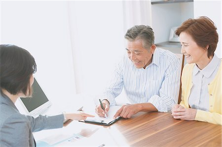 descriptive - Senior Japanese couple consulting with financial planner Stock Photo - Premium Royalty-Free, Code: 622-08122709