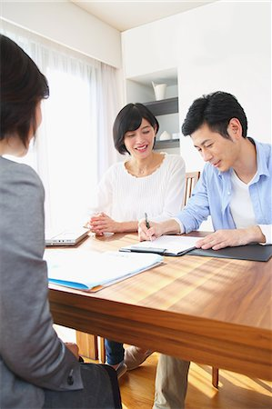 descriptive - Young Japanese couple consulting with financial planner Stock Photo - Premium Royalty-Free, Code: 622-08122703