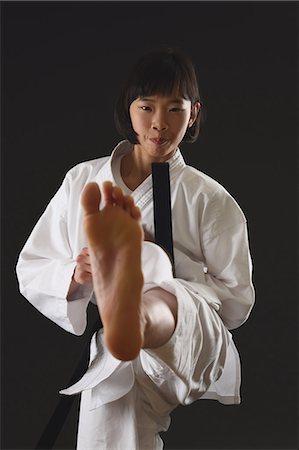 preteen feet - Japanese kid in karate uniform on black background Stock Photo - Premium Royalty-Free, Code: 622-08657694